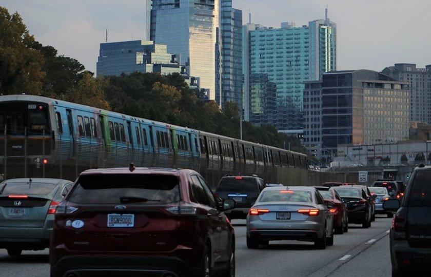 Freeway traffic travels beside a MARTA train, with Buckhead skyline in background
